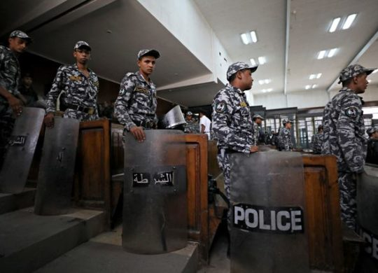 Police stand guards during a court session in which 739 people are being tried for participating in a 2013 sit-in in support of the Muslim Brotherhood. in Cairo